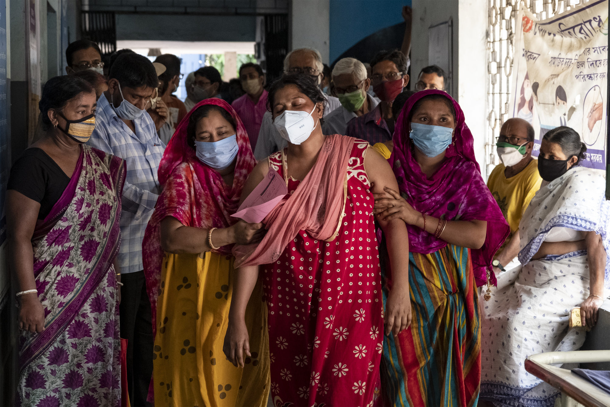 crowd of citizens with medical face masks ushering a woman through a hallway